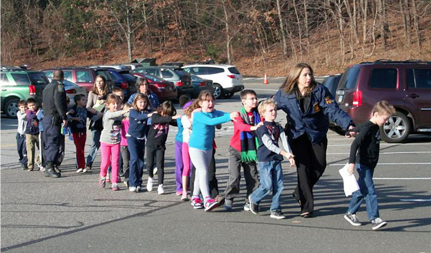 State police personnel lead children from the Sandy Hook Elementary School in Newtown, Conn.
