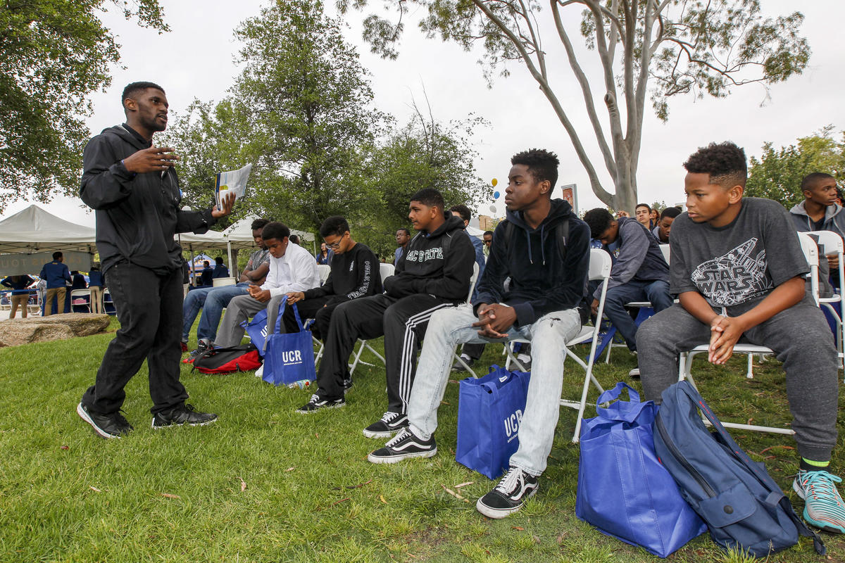 Admissions counselor De'Von Walker, left, speaks to young students visiting UC Riverside through the Council of African American Parents program on Highlander Day.