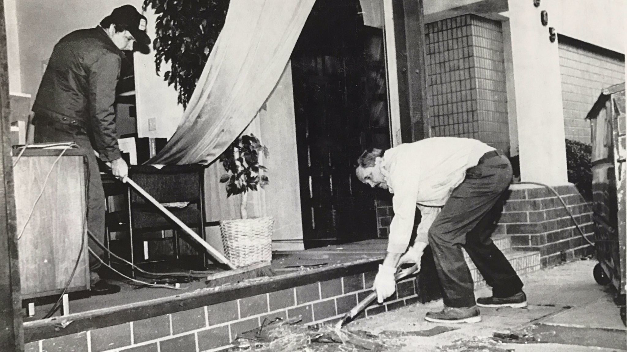 Ronald Cloutier shovels plate glass as Javier Surrano sweeps glass from offices of Diversified Maintenance Services after a 5.0 earthquake hit south Pasadena in 1988.