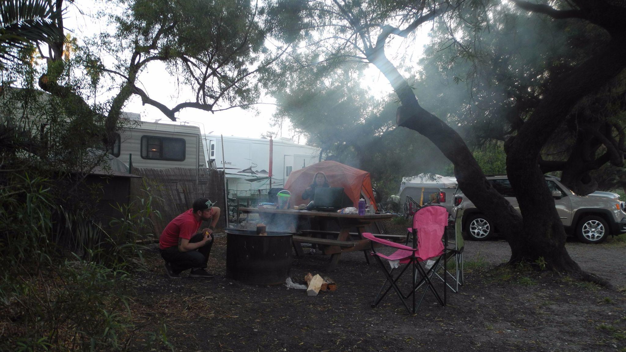 Elyie Florez blows into the fire in Refugio State Beach campsite while writer Denise Florez prepares the stove to sauté vegetables, May 20, 2017.