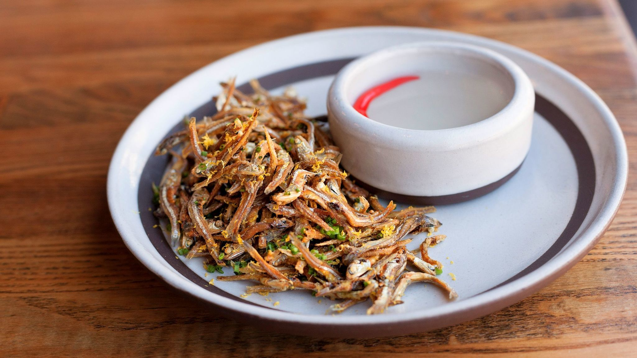 Dried and fried anchovies are a beloved Filipino snack, served exquisitely at Irenia with a pungent infused vinegar for dipping.
