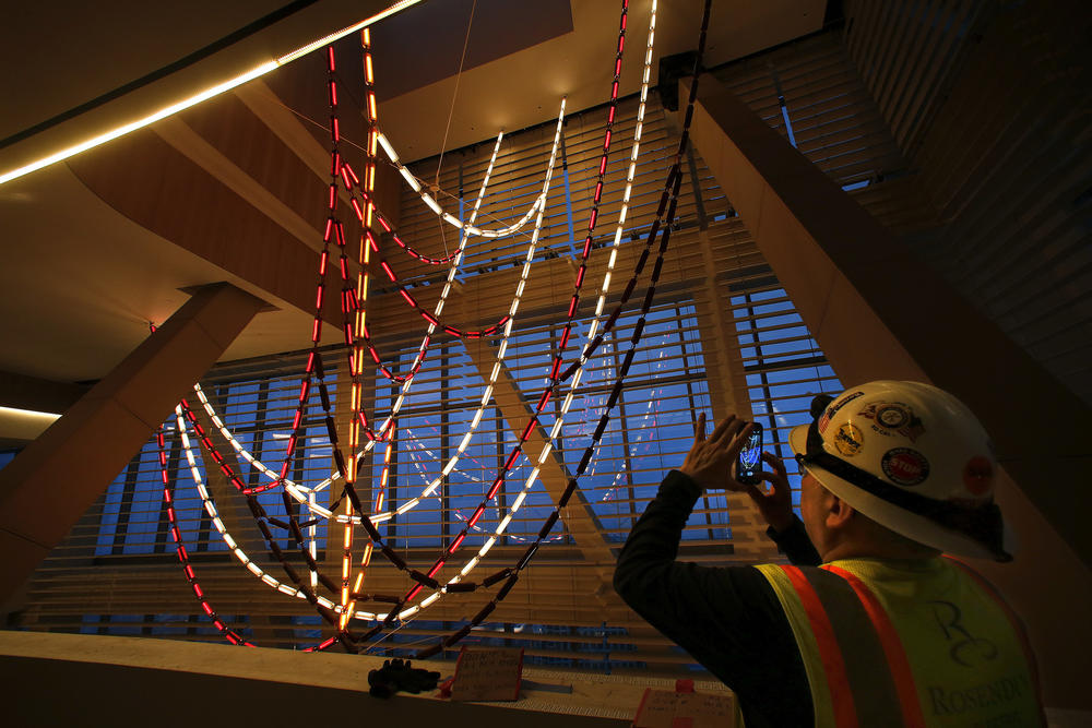 A construction worker photographs the three-story-high chandelier.