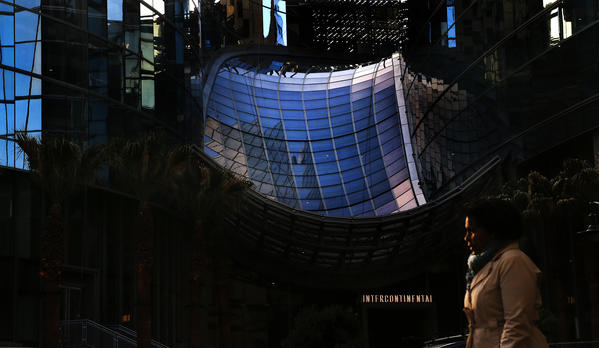 A pedestrian walks along Figueroa Street in downtown Los Angeles with the skylight of the Wilshire Grand seen in the background. (Mel Melcon / Los Angeles Times)