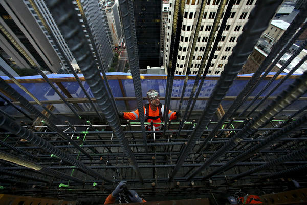Iron worker Javier Jimenez guides a rebar wall into position. (Mel Melcon / Los Angeles Times)
