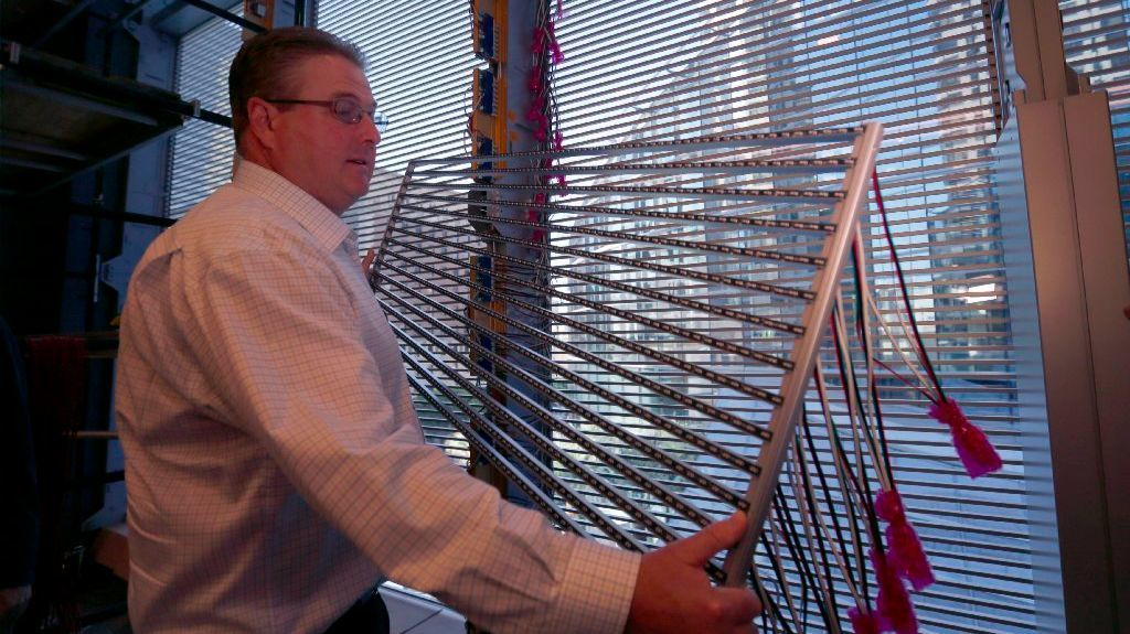 James Hart, StandardVision construction director, holds a section of the LED screen at the Wilshire Grand Center.