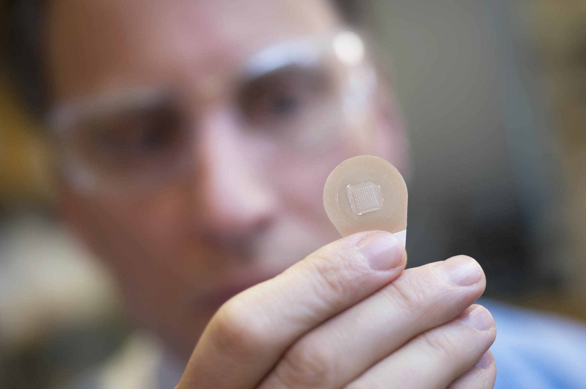 Mark Prausnitz, who develops microneedle technology at Georgia Tech, holds a vaccine patch containing needles that dissolve into the skin.