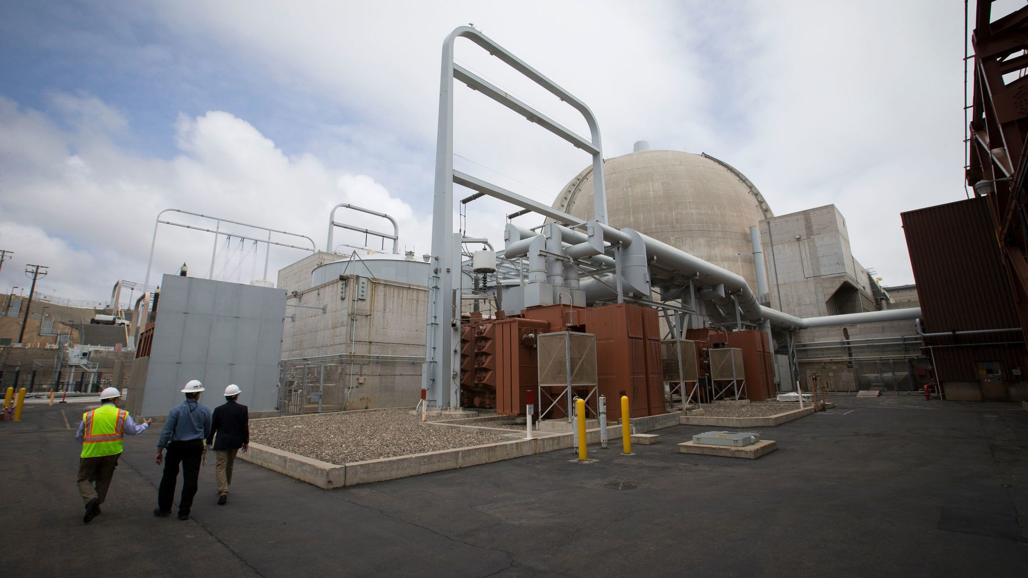 Thomas Palmisano, left, decommissioning and chief nuclear officer, and Lou Bosch, center, Southern California Edison plant manager, lead a tour near the electricity switch yard where two-thirds of the used nuclear fuel is in wet storage.