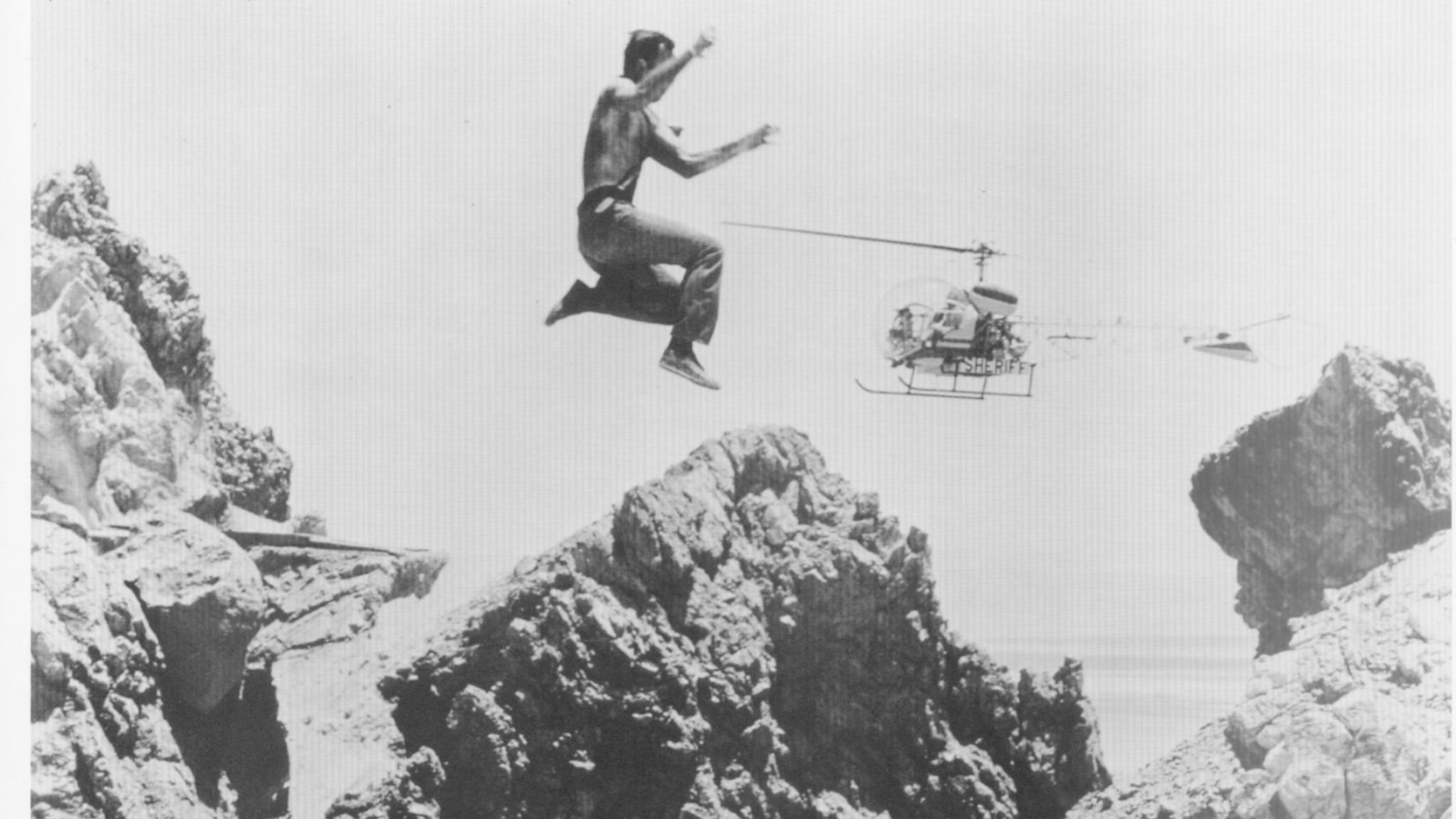 "Loren Janes leaps during a scene from the television show ""The FBI."""