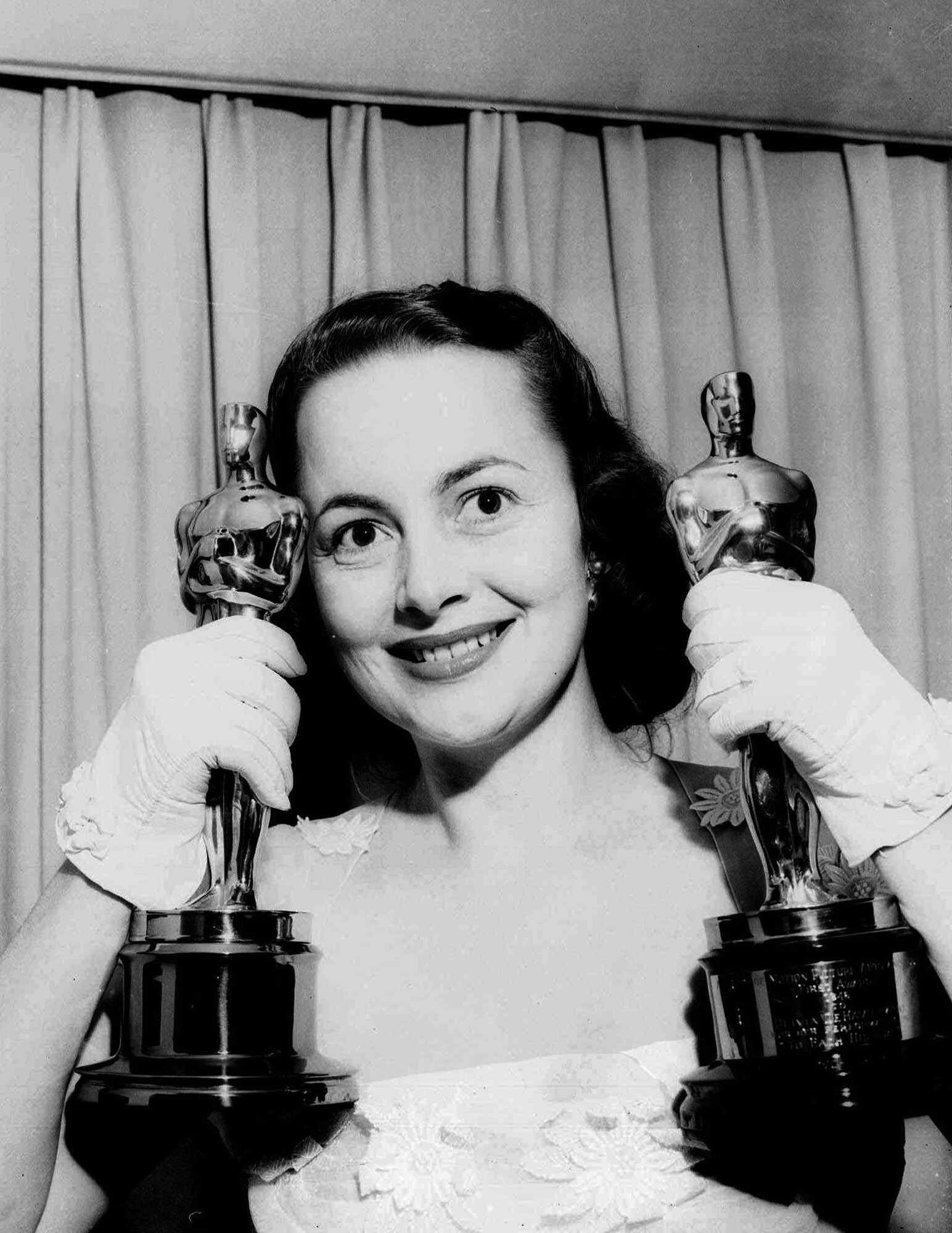 Olivia de Havilland holds her two Academy Award statuettes in March 1950. (Associated Press)