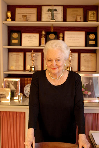 Actress Olivia de Havilland poses with her accolades at home in Paris in 2003.