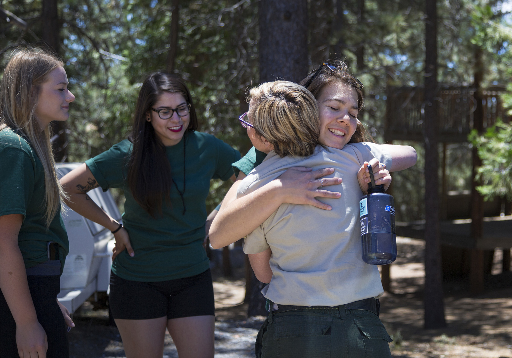 Adela Montserrat Valencia of Cameron Park, holding a water bottle, gets a hug from Kristen Allison of the U.S. Forest Service after graduating from the training camp.