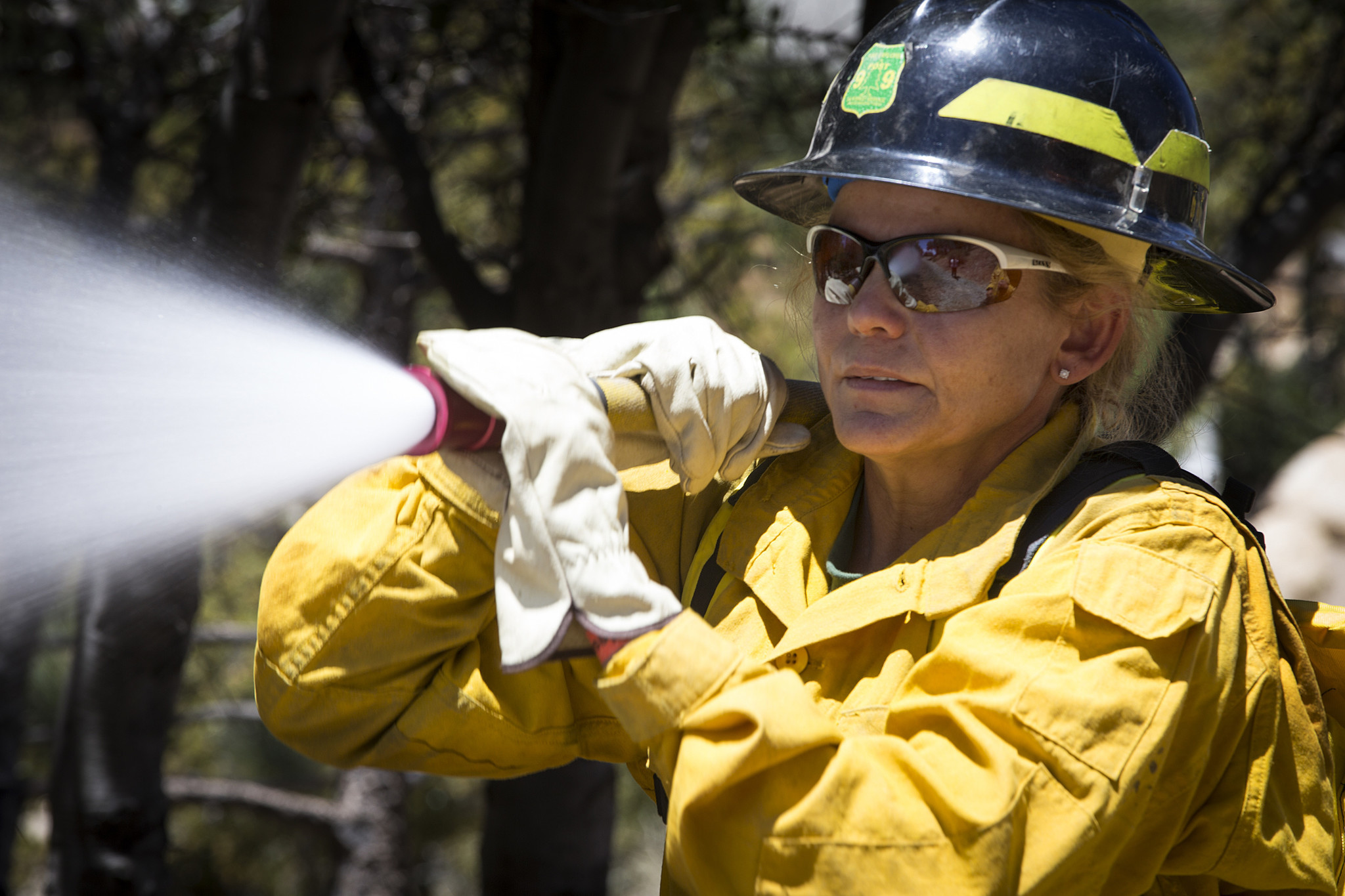 Yasmine Wolfe, a property manager from Sunland, operates a fire hose.