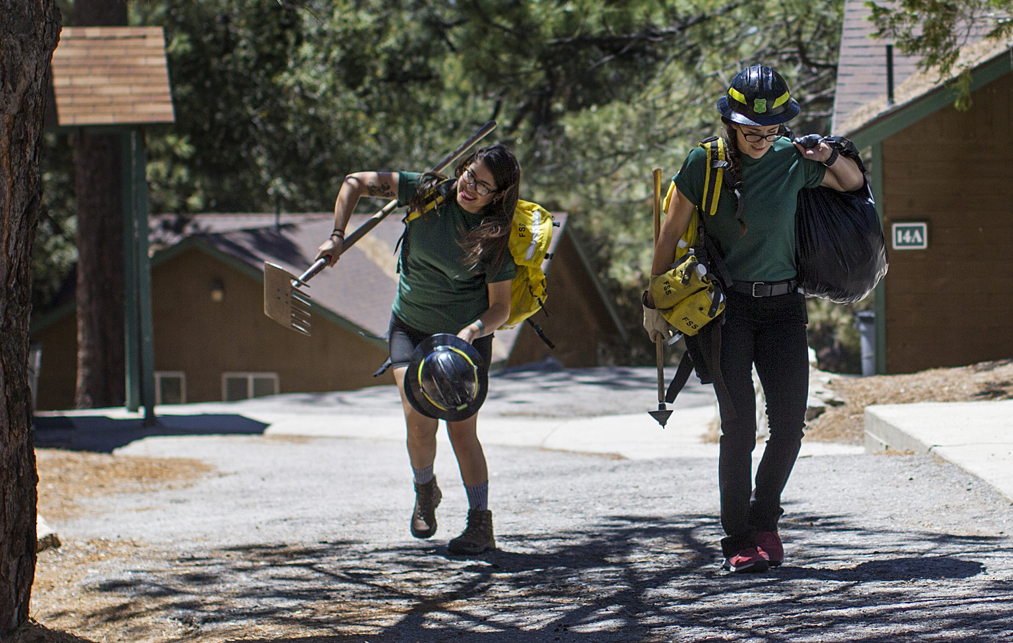 L.A. art teacher Estephany Campos, left, and Inglewood sales clerk Kelsey Almendariz pack up their hand tools after graduating from the Women in Wildland Fire Basic Training Camp.