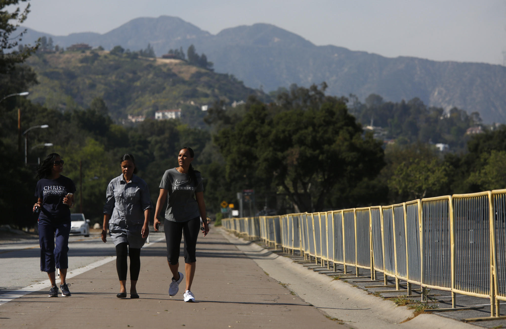 Walkers make their way along West Drive on a walk around the Rose Bowl in Pasadena.