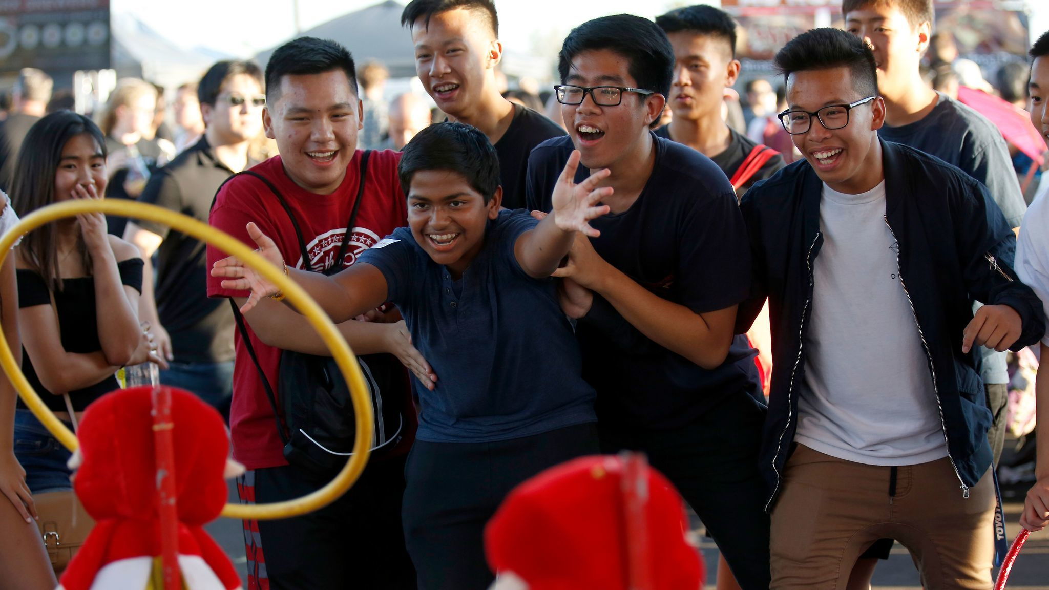 Roshan Kannan, 15, center, of Arcadia, is surrounded by friends as he tosses a ring in hopes of winning a stuffed animal at the 626 Night Market in Arcadia.