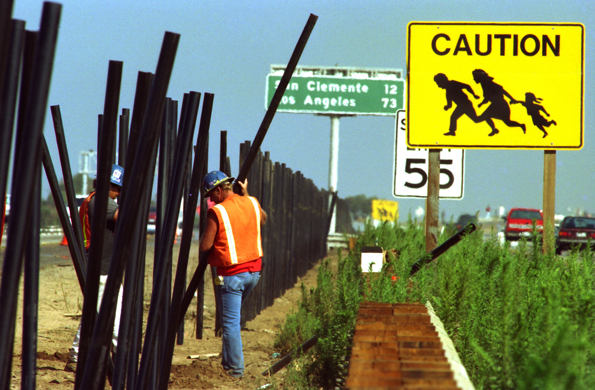 Contractors in 1993 set posts for an 8-foot fence in the median of the 5 Freeway in the shadow of an iconic yellow pedestrian warning sign.