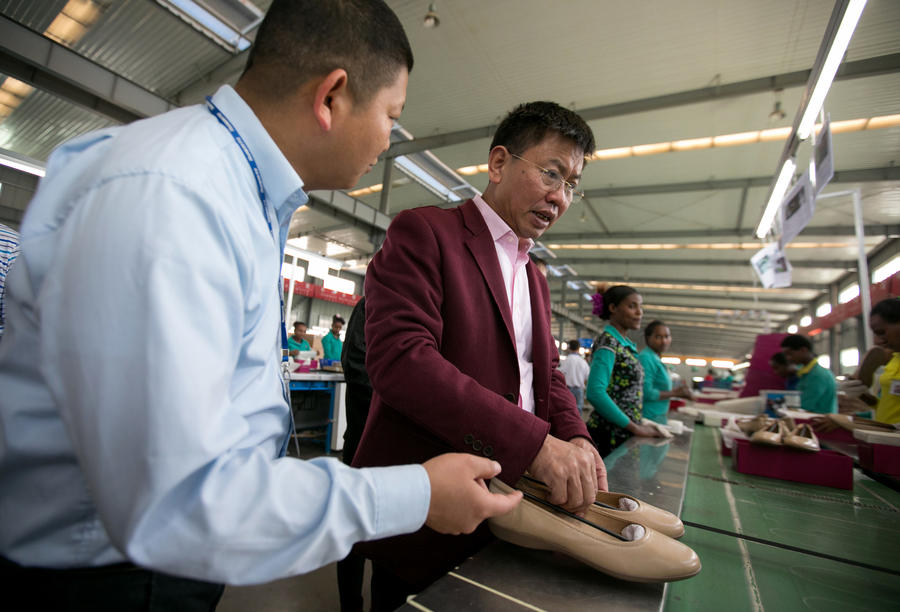 Zhang Huarong, chief executive of Huajian Shoe Co., inspects the production lines. — Photograph: Noah Fowler/Los Angeles Times.