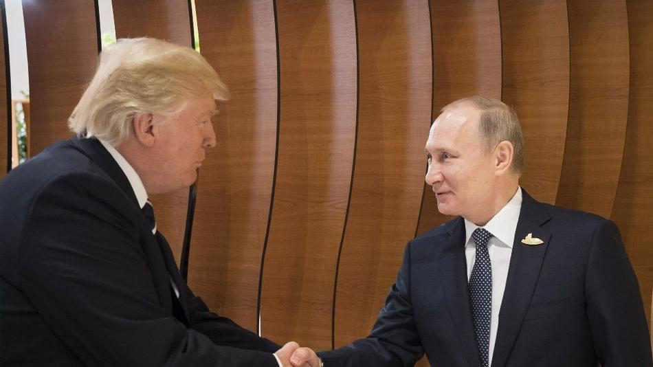 President Trump left shakes hands with Russian President Vladimir Putin