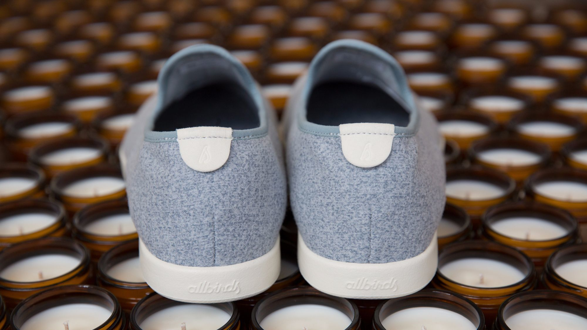 Allbirds and P.F. Candle Co. wool Lounger with off-white sole, $95; and soy candles, which include notes of moss, sweetgrass, vetiver, cedarwood and honey, $18.