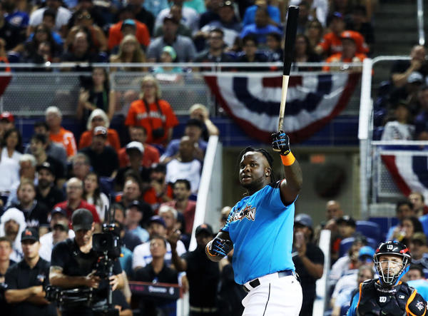 Miguel Sano admires one of his homers Monday night. (Rob Carr / Getty Images)