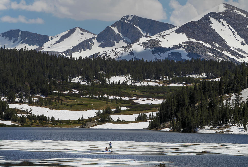 In early July, two standup paddle boarders skim along the icy waters of Tioga Lake off Highway 120.