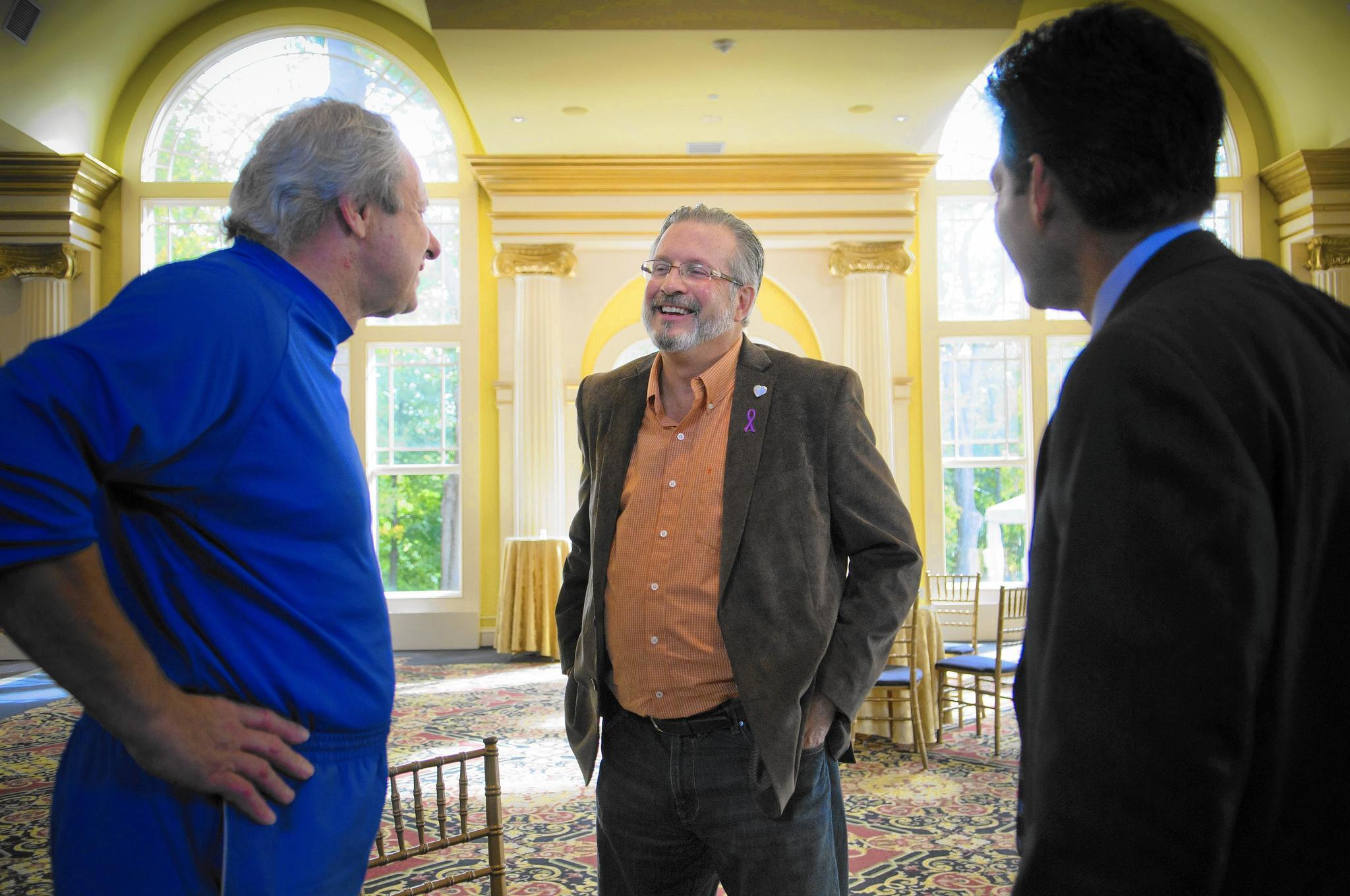 William Petit talks with Central Connecticut State University basketball coach Howie Dickenman, left, and Hartford attorney Eric Daniels at The Riverview in Simsbury where Petit was attending the launch of a social media campaign by The Interval House.