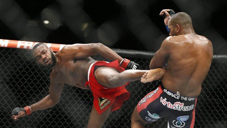 Jon Jones kicks Daniel Cormier during their light heavyweight title mixed martial arts bout at UFC 182 on Jan. 3, 2015. (John Locher / Associated Press)