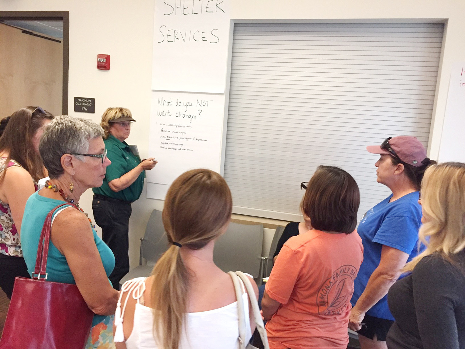 Attendees give their input on shelter services they do not want changed as resident Terri Halverson writes them down.