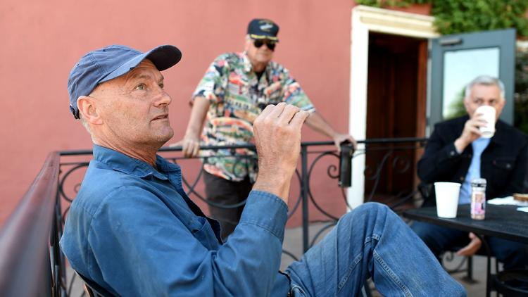 Bill Dettmer, left, tells neighbors gathered at Madhouse Coffee in Brisbane, Calif., why he's in favor of the proposed 4,400-home project. (Josh Edelson / For The Times)