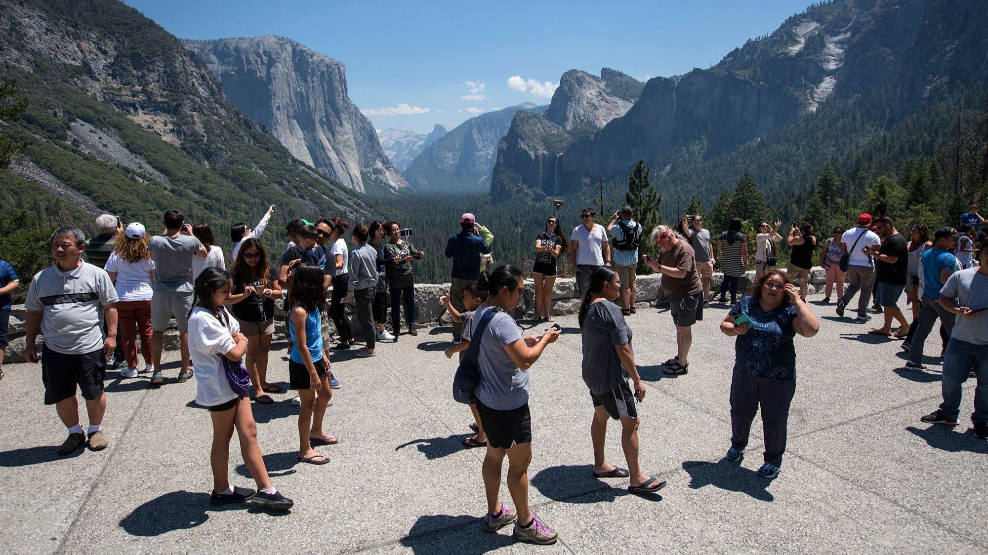 Visitors crowd Yosemite's Tunnel View overlook.