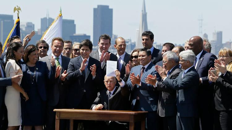Gov. Jerry Brown signs an extension of California's cap-and-trade program in July. (Eric Risberg / Associated Press)
