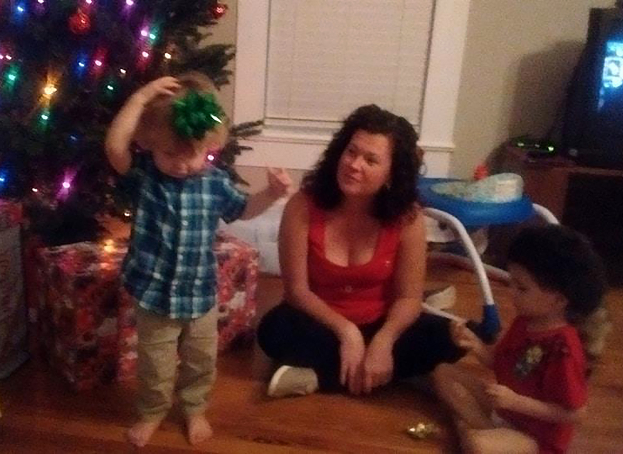 Family snapshots and video from Christmas Day 2016 show Heather and Daniel Kelsey smiling and sitting on the floor next to a tree trimmed with colored lights as their boys tear open their gifts. (Courtesy Mike Belisle)