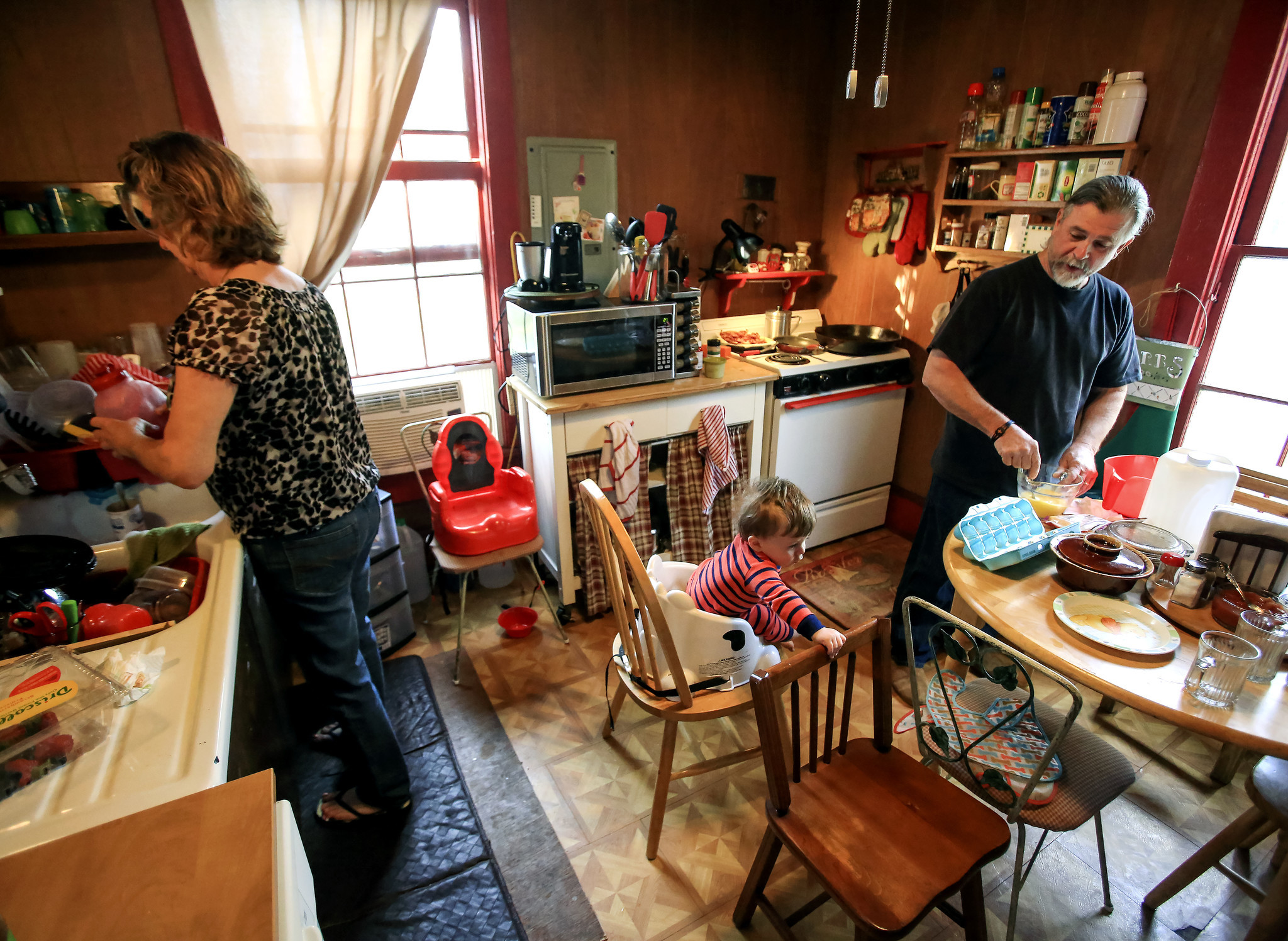 Mike and Lynne Belisle prepare breakfast in their kitchen while Mike also keeps an eye on one-year-old Nicholas at their Quincy home.