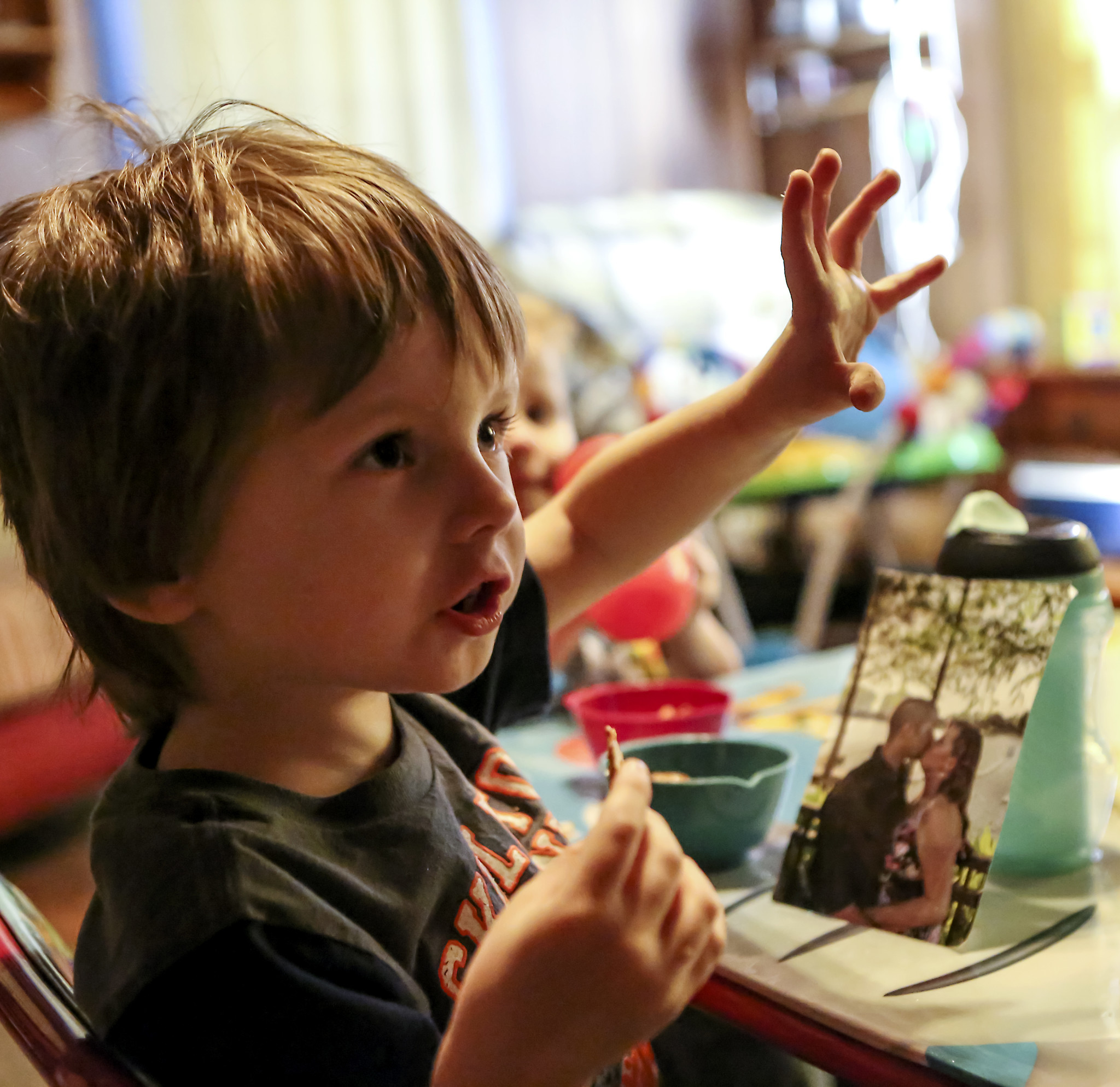 Joey Kelsey, 5, eats a snack after he rests a photo of his parents against his cup.