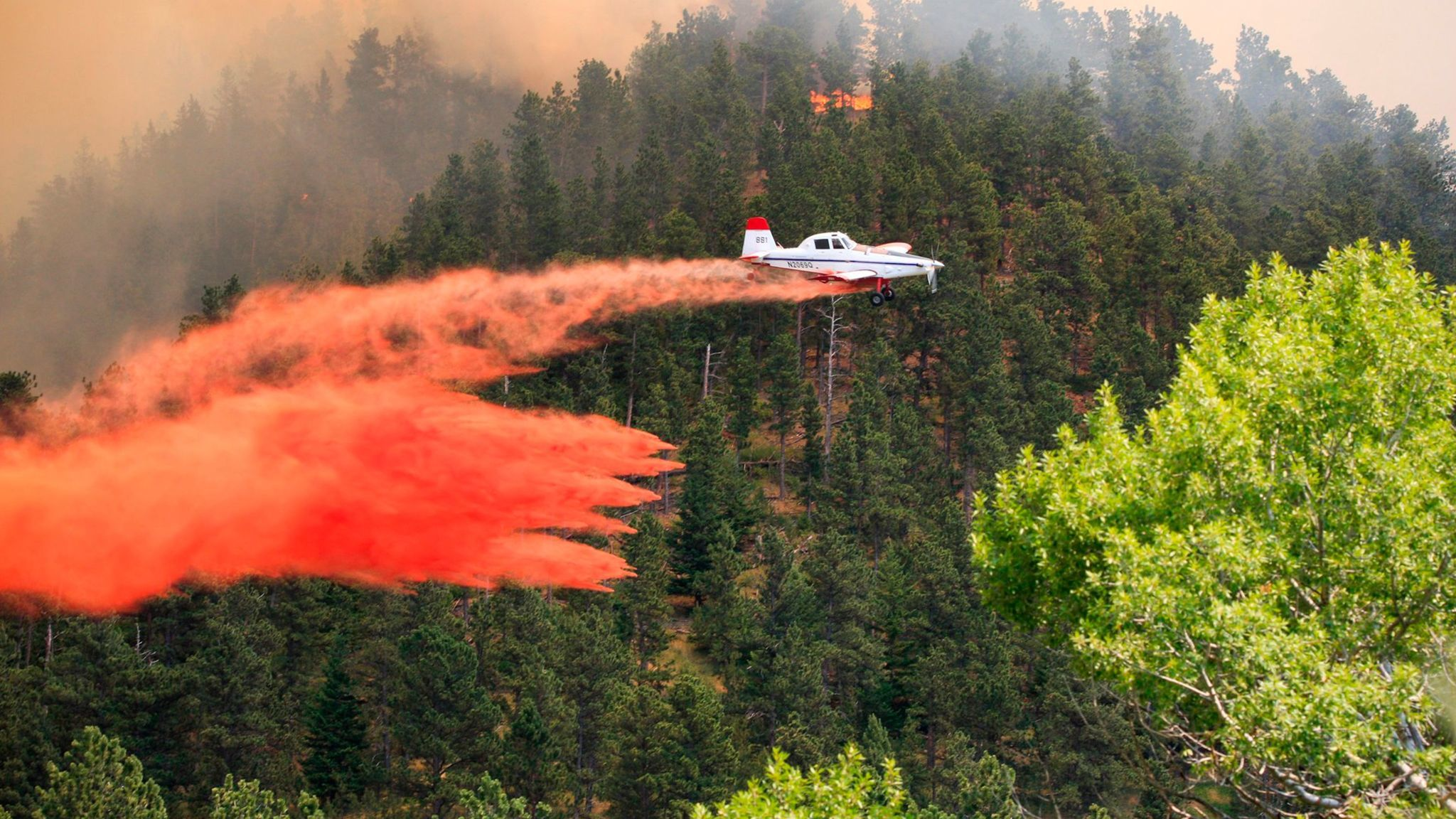 A plane drops retardant on a wildfire near the historic mining town of Landusky, south of the Fort Belknap Indian Reservation in north-central Montana.