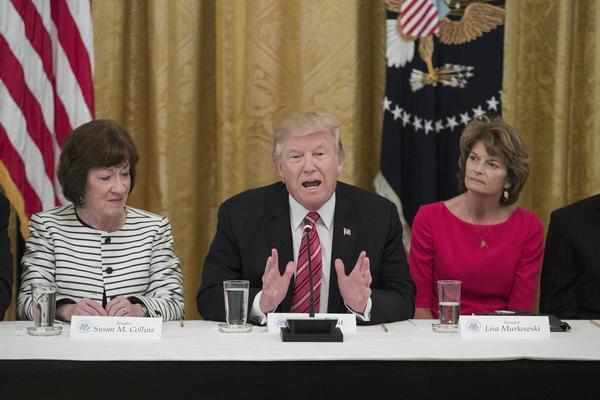 President Donald Trump delivers remarks beside Republican Senator from Maine Susan Collins, left, and Republican Senator from Alaska Lisa Murkowski. (Michael Reynolds / European Pressphoto Agency)