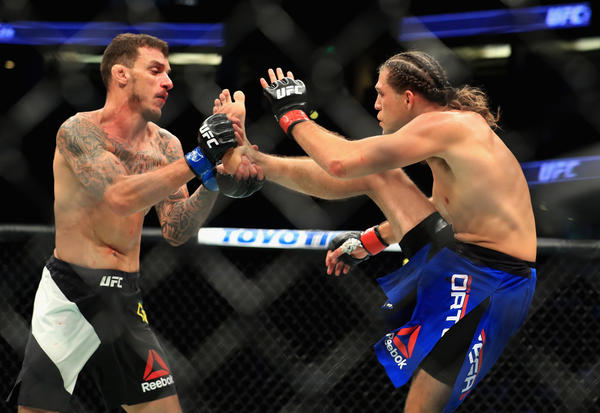 Renato Moicano, left, tries to block a kick by Brian Ortega during their featherweight bout at UFC 214. (Sean M. Haffey / Getty Images)