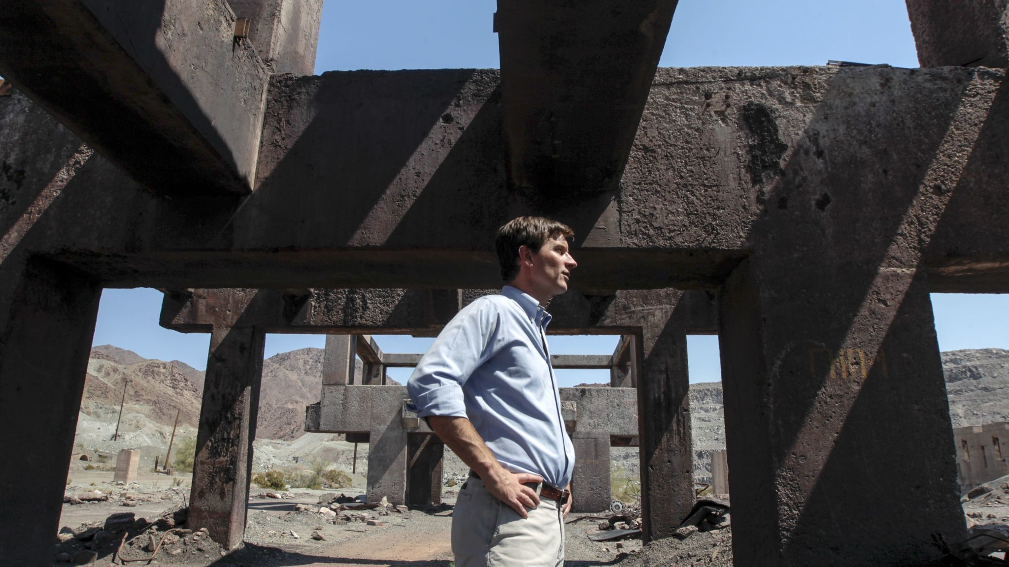 Steve Lowe, president of Eagle Crest Energy Co., stands amid the ruins of the ore loading area.