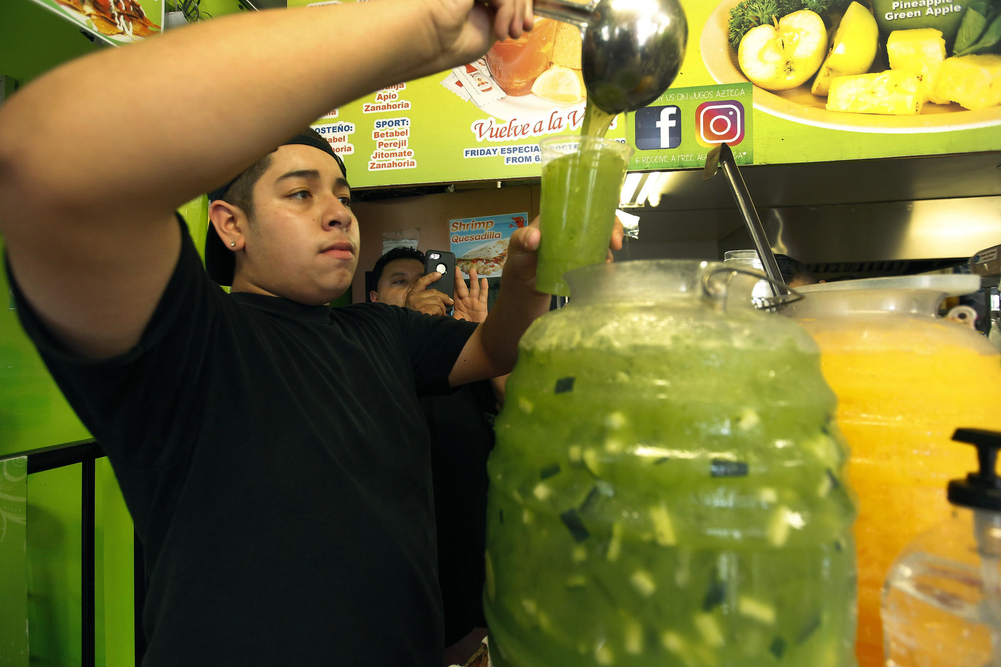 Randy Peña, 14, pours a juice for a customer.