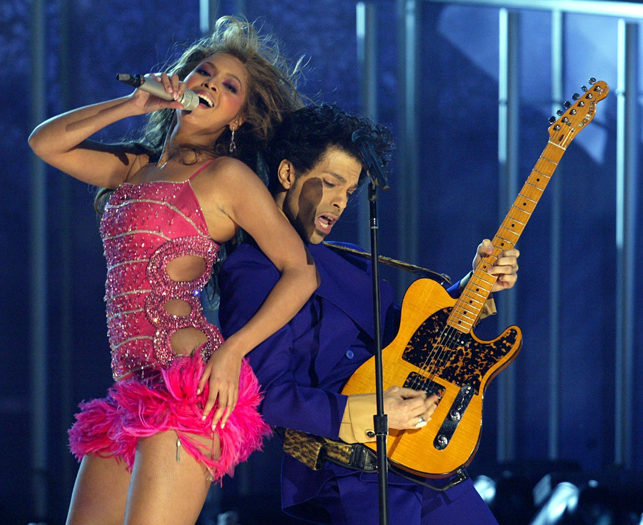 Beyoncé, left, and Prince perform together at the Grammy Awards in 2004. Bey penned the foreword to a new book of photographs of the late pop superstar. (Timothy A. Clary / AFP/Getty Images)