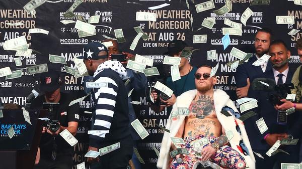 Money rains down on Floyd Mayweather, front left, and Conor McGregor during a media event in Brooklyn, N.Y. on July 13. (Mike Stobe / Getty Images)