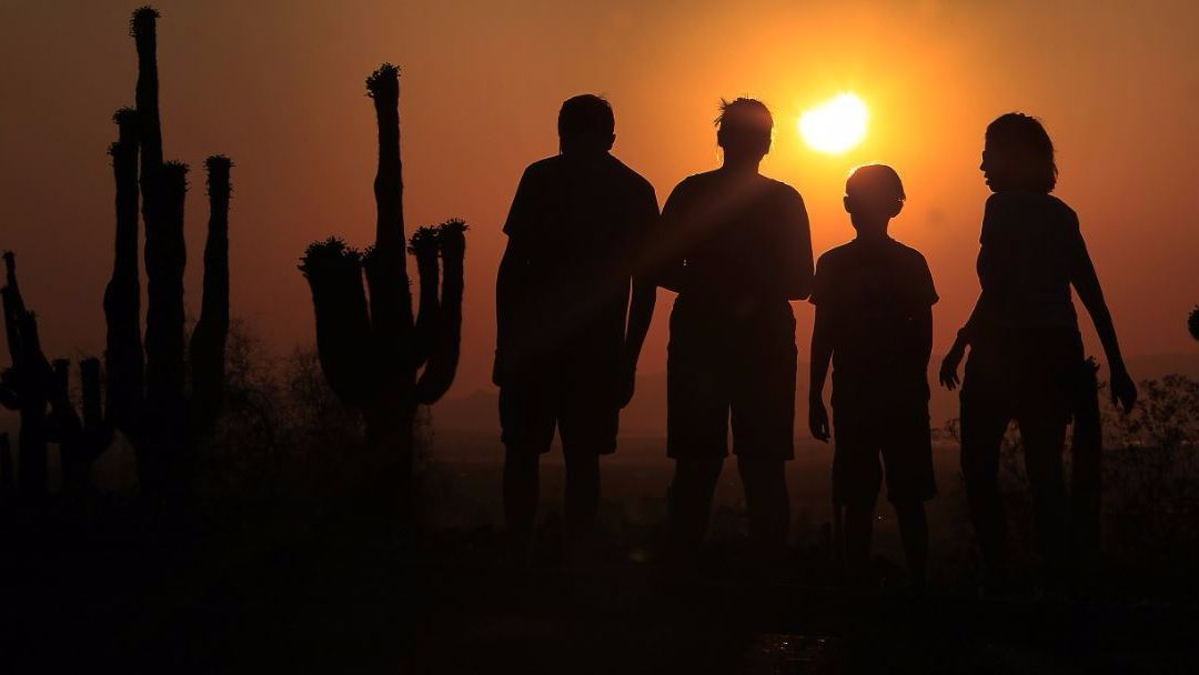 People view an annular solar eclipse as they look toward the setting sun on the horizon in Phoenix in May of 2012.