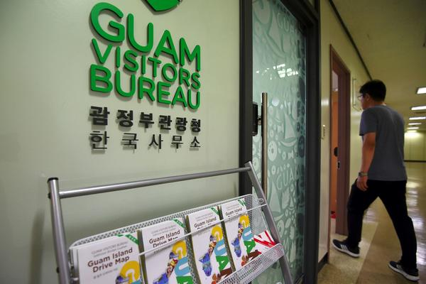 A man walks past the Seoul office of the Guam Visitors Bureau in Seoul