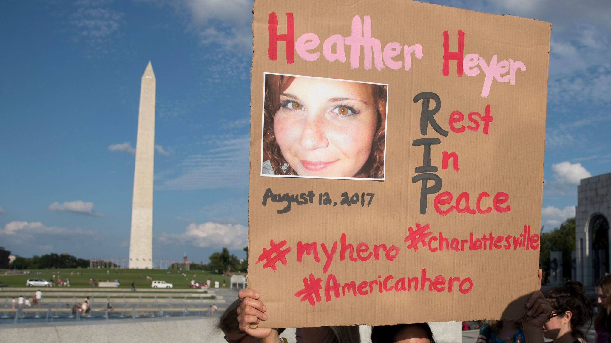 A woman holds a sign honoring Heather Heyer, a victim of this weekend's violence in Charlottesville, Va.,