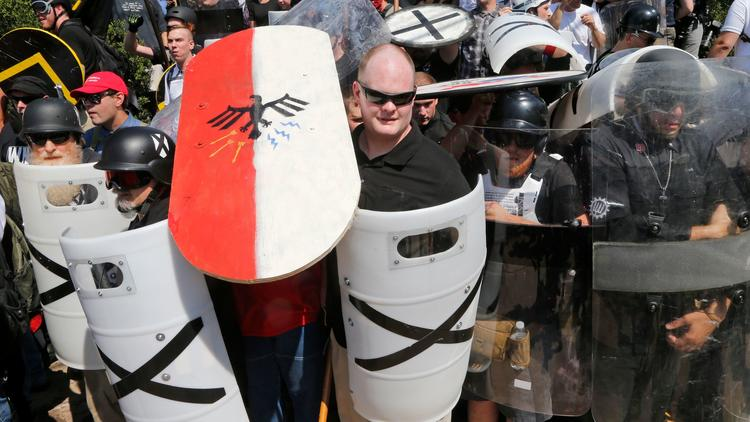 White nationalist demonstrators use shields as they guard the entrance to Lee Park in Charlottesvill