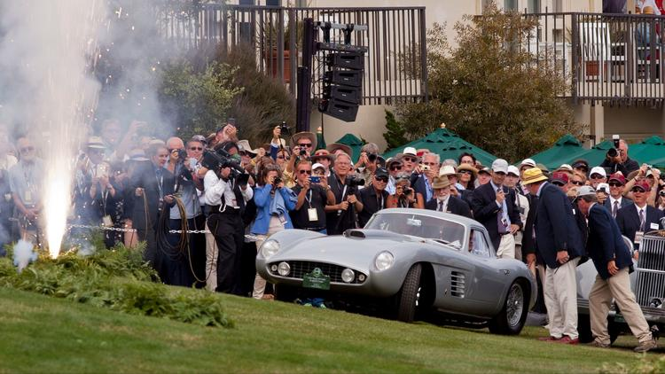 Fans and judges watch a 1954 Ferrari 375 MM Scaglietti Coupe drive up to accept the Best of Show awa