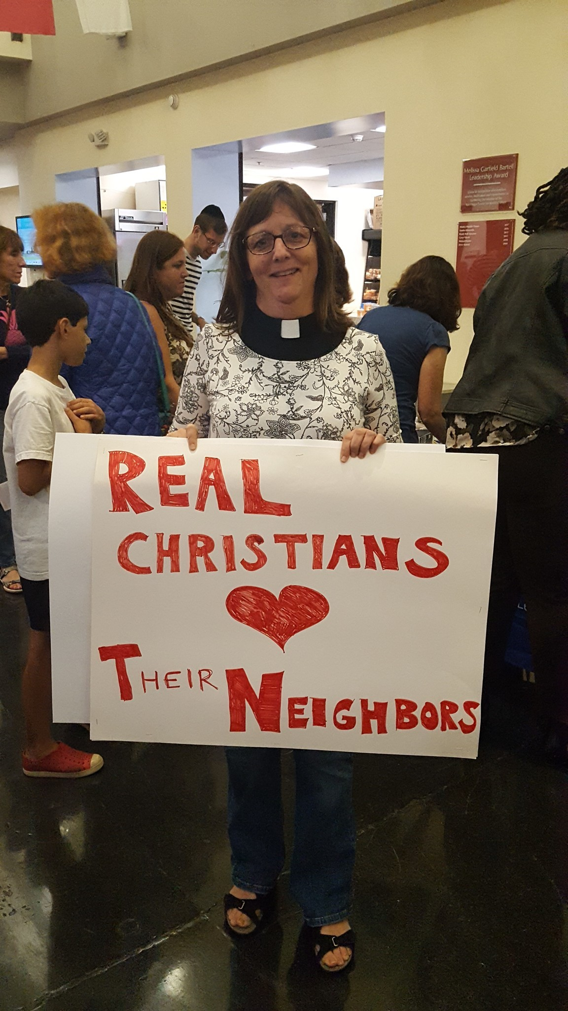 "A Christian supporter with a sign that reads ""Real Christians love their neighbors."""