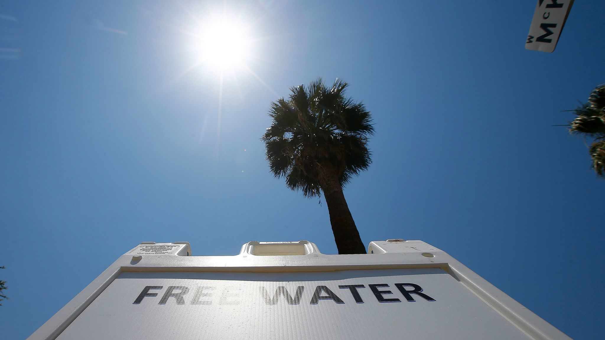 A Salvation Army hydration station sign sits in the midday sun as the temperature climbs to a near-record high in Phoenix.