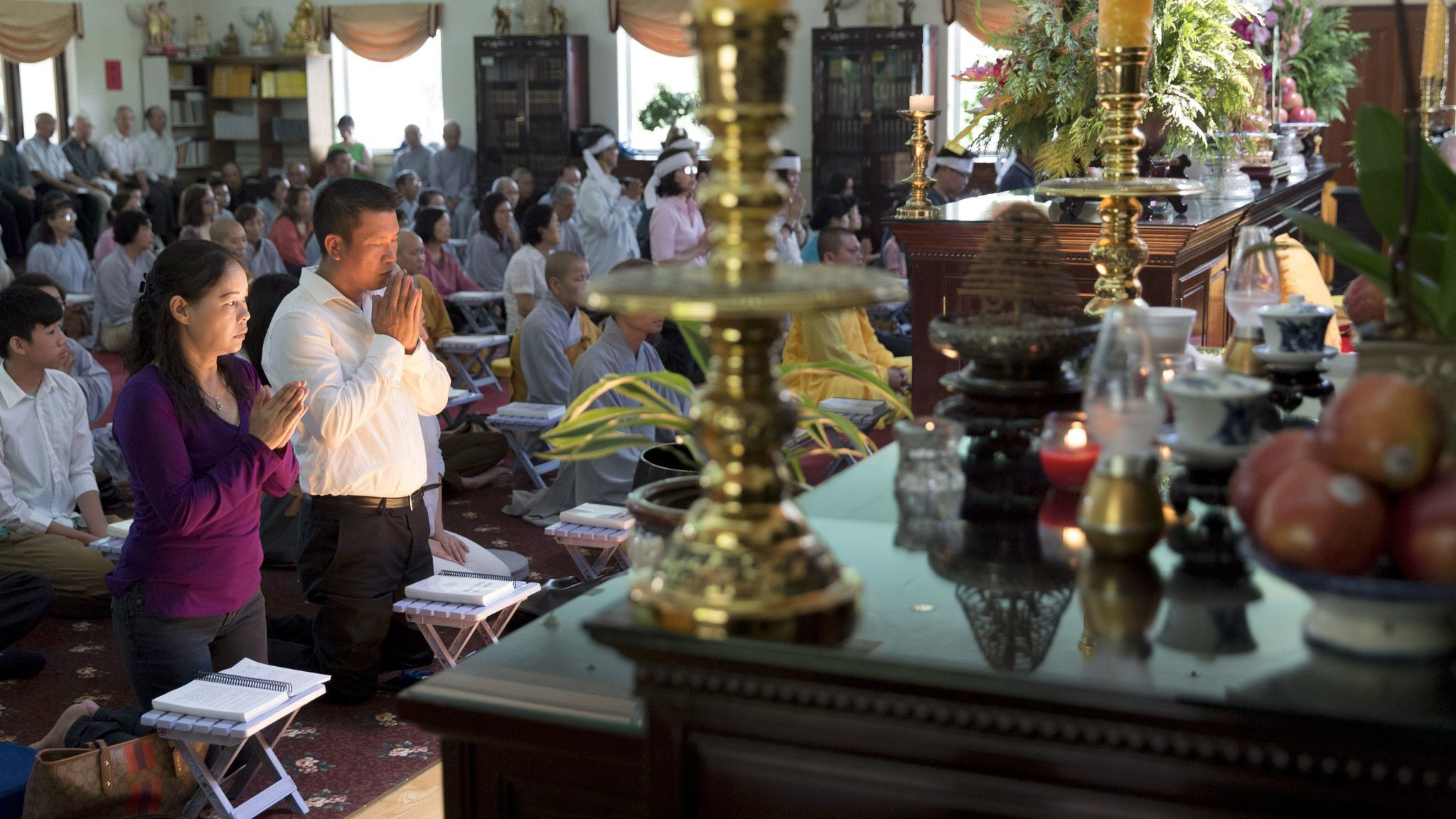 Dieu Ho, left, and Hoai Le pray for son Tommy Le at his reincarnation ceremony in August..
