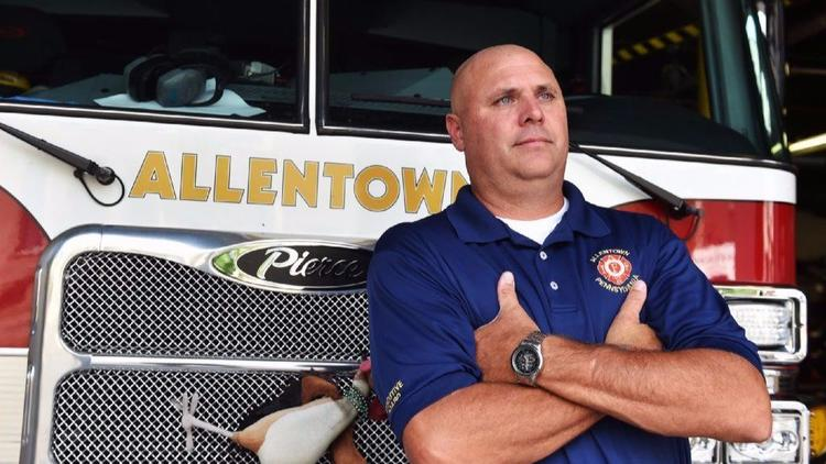 Jeremy Warmkessel, president of Fire Fighters Local 302 in Allentown, stands in front of Engine 4 at
